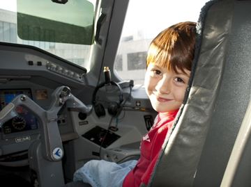 A child participating in Wings for Autism, inside a plane.